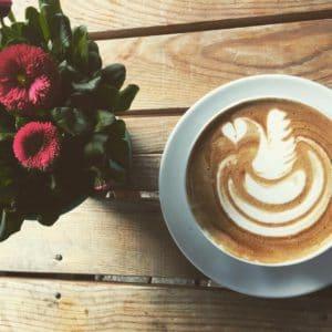 Tasse Kaffee und Blumenstrauß